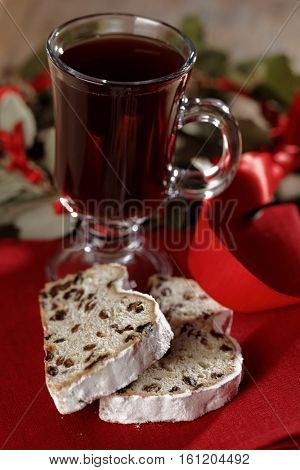 Slices of Christmas stollen and a glass of mulled wine on a rustic table