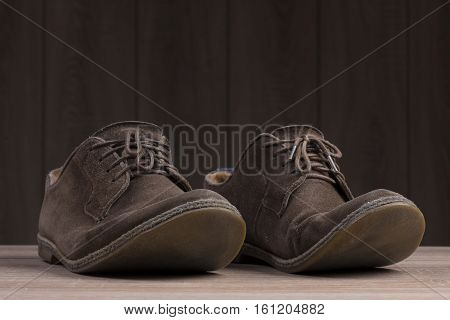 Brown suede shoes with brown laces on the background of dark natural wood.