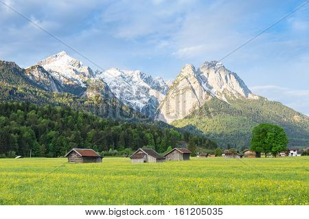 Bavarian serene landscape with snowy Alps mountains ridge and spring flowering pasture in valley. Springtime morning panoramic scenic view stock photo captured from Garmisch-Partenkirchen side.