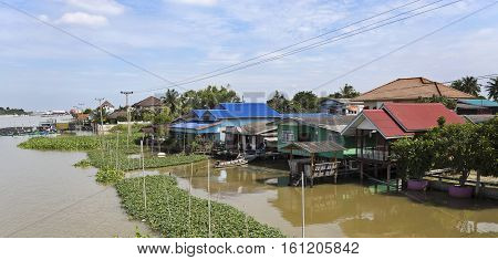 Traditional Thai village by the water on the banks of the Chao Phraya River in Ayutthaya Thailand