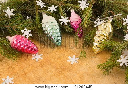 The branches of Christmas trees and fallal cone decorations on the background of wooden boards and snowflakes. Christmas and New Year's background.