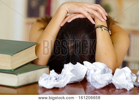 Young brunette woman wearing pink top lying bent over desk with stack of books placed on it, wasted papers around, appears to be sleeping, tired student concept.