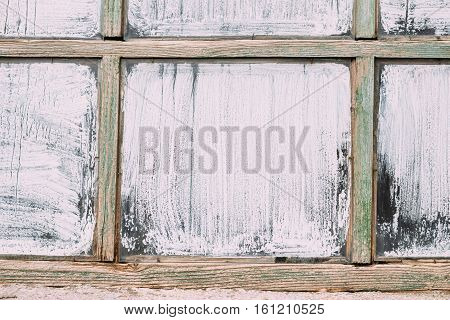 Old wooden window on an old house green frame and white glass