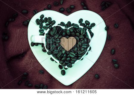 Coffee klatsch java concept. Heart shaped white cup filled with roasted coffee beans on brown cloth background