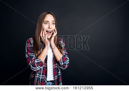 Can not hide the feelings. Emotional young beautiful woman holdign her hands on the face and feeling scared while standing isolated on black background
