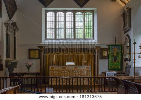 Grasmere England - May 30 2012: The chancel of the Saint Oswald Church is well lighted by a large window above the altar. Paintings and tablets decorate the walls. Candle and book on altar.