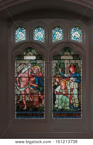 Grasmere England - May 30 2012: Bright colored stained glass window at Saint Oswald Church shows scene out of Jesus life. Set in dark wall with smaller windows. Jesus tells to release a naked captive man.
