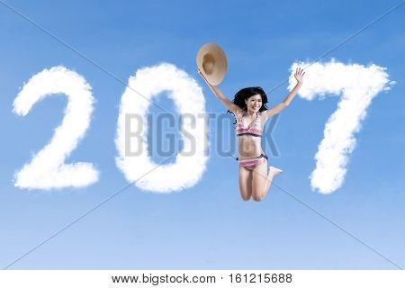 Concept of New Year 2017. Picture of of cheerful woman leaping on the sky with number 2017 and wearing swimsuit
