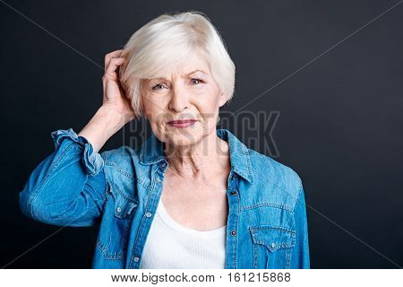 Let me think. Pleasant elderly woamn holding her hand on the head and feeling confused while being involved in thoughts