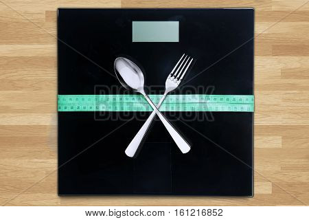 Close up of measuring tape and crossed cutlery on a weigher machine with wooden background