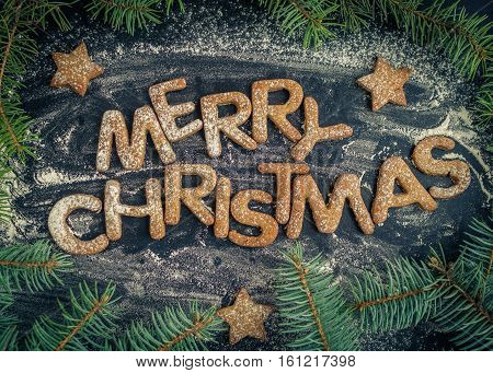 Phrase Merry Christmas from homemade gingerbread cookies on dark chalkboard background. Christmas concept. Christmas moody style greetings card. Happy New Year. Top view.