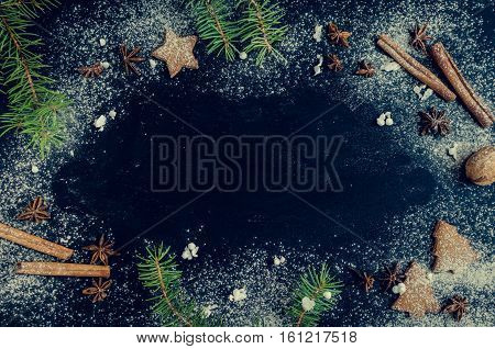 Christmas fir tree with gingerbread cookies cinnamon anise and snow on chalkboard background with space for text. Merry Christmas and Happy New Year. Xmas concept. Top view. Copy space.