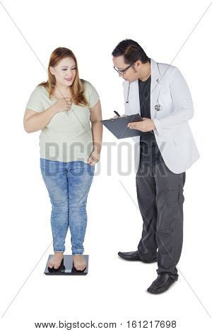 Image of young male doctor holding a clipboard and measuring the weight of his patient while writing the report isolated on white background