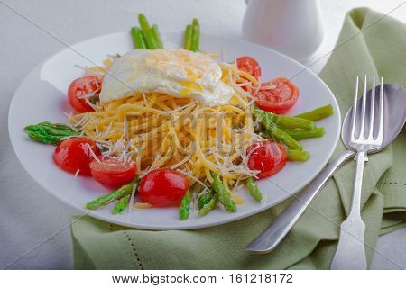 Spaghetti with egg and vegetables on a white plate
