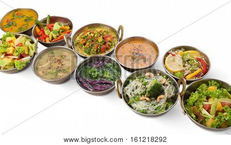 Vegan or vegetarian restaurant dishes, hot spicy indian soups and salads in copper bowls. Traditional indian cuisine meal assortment isolated on white background. Healthy eastern local food