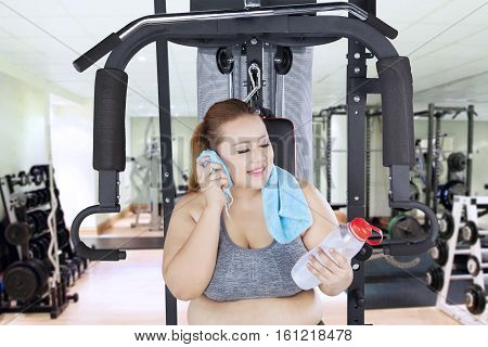Exhausted obese woman after workout and wiping his sweat while holding mineral water at the gym