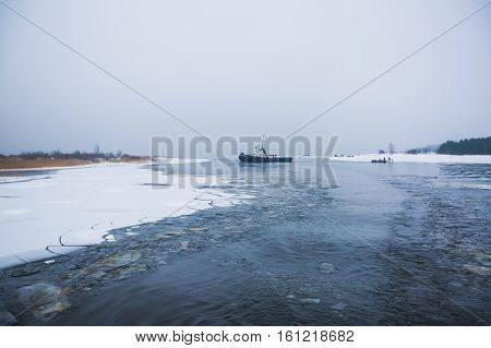 The russian Icebreaker tug boat ship trapped in ice tries to break free and leave the bay between the glaciers