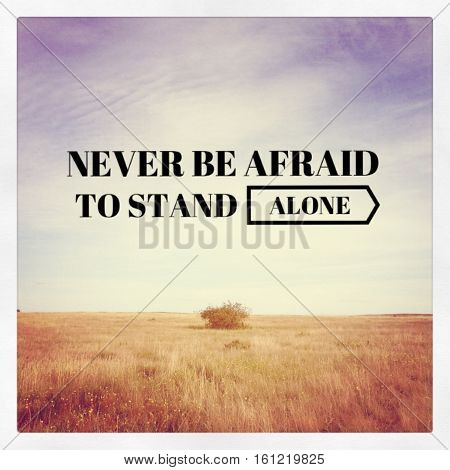 Never be afraid to stand alone. Isolated bush in prairie field with motivational quote.  Inspirational quote on prairie field landscape.  Instagram effects.