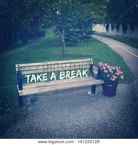 Inspirational quote on isolated unoccupied wooden park bench with pink flowers in pot alongside of paved trail.  White fence with vines and lush green grass and tall green trees in background.