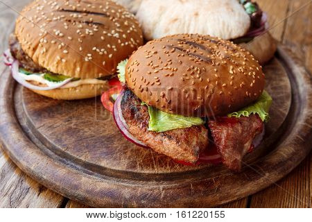 Classic american fast food background. Burgers with grilled on barbecue steak meat and onions on wood. Hamburgers with fresh vegetables composition.