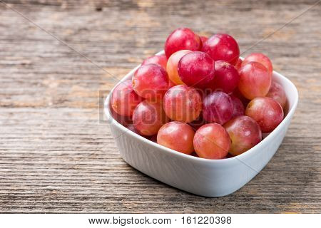 Grapes in bowl on the wooden table in natural light