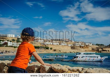 boy child is looking from the mountain to the beach with blue sea and nice boat yacht