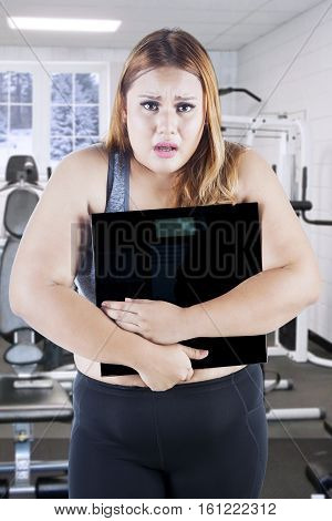Portrait of obese female holding scales and looking at the camera while standing on the fitness center