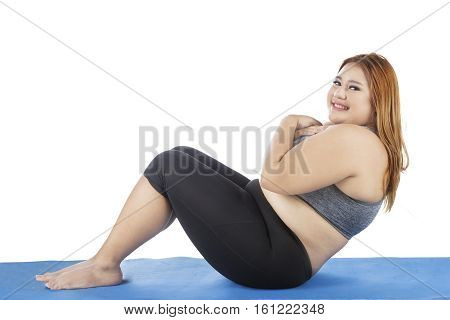 Picture of obesity woman doing sit up exercise on the blue mat while smiling at the camera isolated on white background
