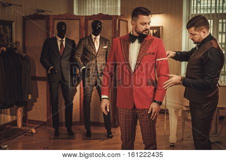 Tailor measuring client for custom made suit tailoring