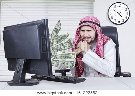 Portrait of pensive middle eastern male entrepreneur looking at money out of computer while sitting in the workplace