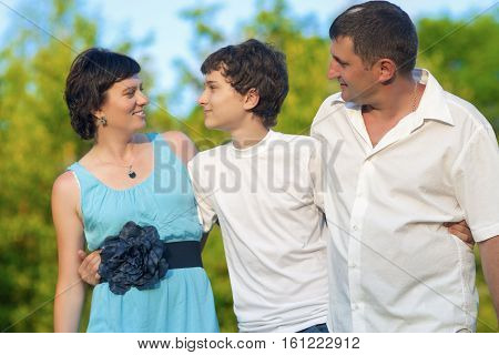 Love and Family Values Concepts. Happy Caucasian Family of Three Spending Time Together. Walking Embraced in Park.Horizontal Image Composition