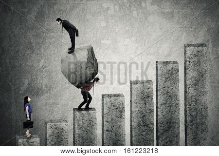 Businesswoman looking at two businessmen standing on a stone and carrying the big stone while walking upward on the chart