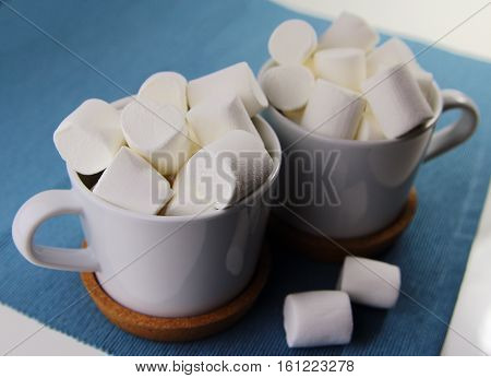 marshmallows in white cups on blue napkin