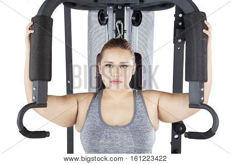 Image of obese female looking at the camera while exercising on a shoulder press machine in the studio