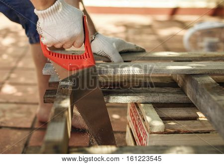 Hands of carpenter working cutting plank with handsaw.