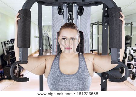 Portrait of overweight woman looking at the camera while exercising on a shoulder press machine in the fitness center