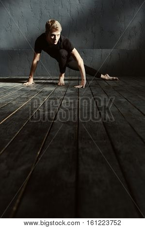 Full of gracefulness. Proficient concentrated young dancer performing in the dark lighted room and having a stretching session while showing his flexibility and expressing grace