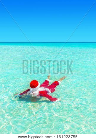 Santa Claus swim and relax in ocean turquoise transparent water. Merry Christmas and Happy New Year travel destinations concept. Vertical natural background.