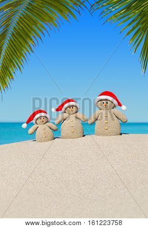 Positive sandy Snowmen family in red Santa hats at sunny ocean tropical palm beach. Happy New Year and Merry Christmas concept for hot travel destinations. Vertical natural background.