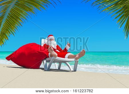 Santa Claus with big red merry Christmas sack thumbs up gesture by hand relax on deckchair at ocean tropical beach under palm leaves. Happy New Year travel destinations concept.