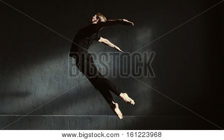 Like a bird . Young flexible expressive man performing in the dark lighted room and dancing while showing his flexibility in the air
