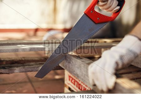 Carpentry woodwork cutting plank with handsaw copy space poster