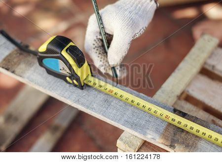 Man's hand doing measure in carpentry woodwork construction.