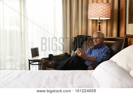 A senior businessman seated on hotel room armchair using his cell phone. Horizontal format with the bed in the foreground