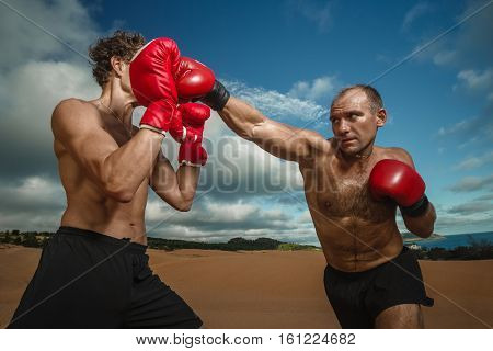 Strong boxer doing  kickboxing exercise with trainer