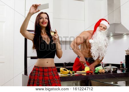 Santa Claus preparing salad at home in kitchen and his woman taking selfie