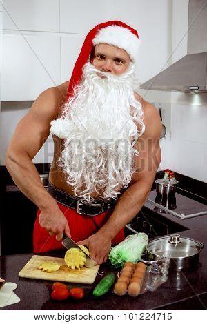 Santa Claus preparing salad at home in kitchen