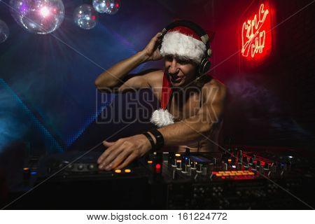 DJ Santa mixing up some Christmas cheer. Disco light around fun, colorful atmosphere.
