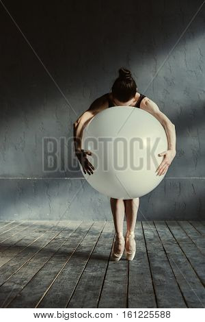 Playing with shapes and sizes. Talented concentrated inspired ballet dancer standing on the tiptoes in the black colored room and hugging the big white balloon while showing the performance