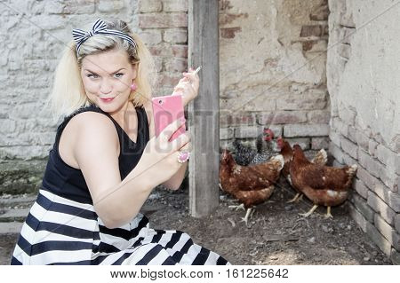 Housewife making selfie next to the flock of hens. Smoking country side fashion style - Smartphone photography
